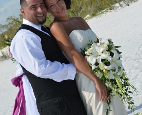Brautpaar mit Brautstrauß am Strand