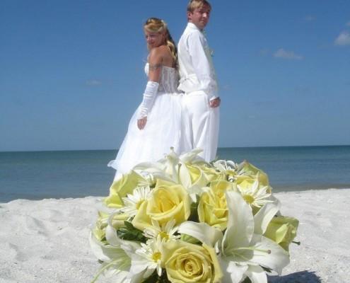 Brautstrauß und Brautpaar am Strand