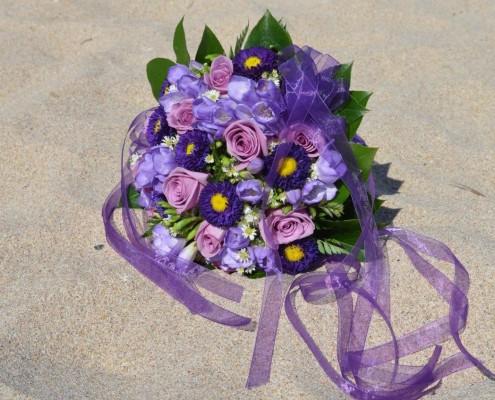 violetter Brautstrauß am Strand